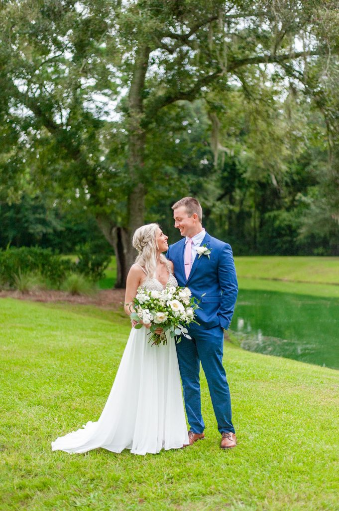 Bride and groom standing in front of pond at Dogwood Downs