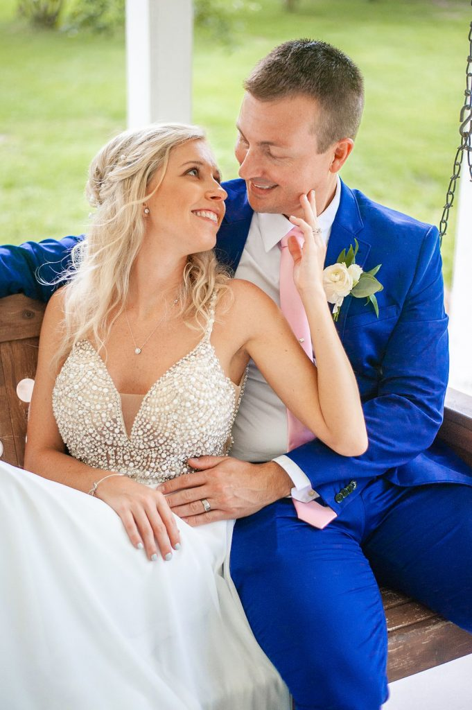 bride and groom sitting on swing at Dogwood Downs